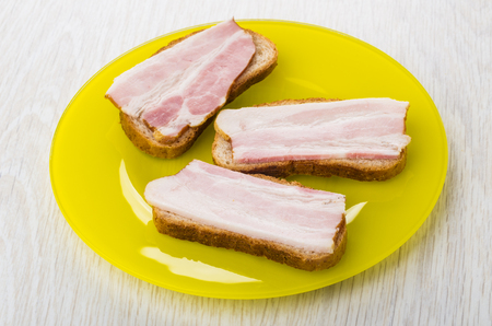 Three sandwiches with bacon in yellow plate on wooden table Zdjęcie Seryjne