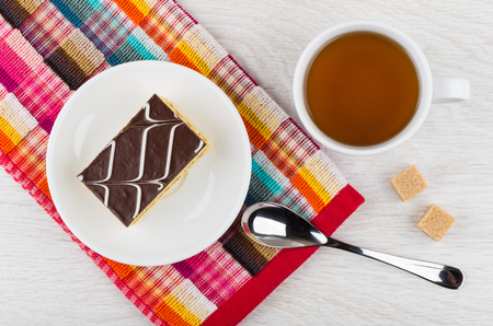 Cake with chocolate in saucer on napkin, sugar cubes, teaspoon, tea in cup on wooden table. Top view