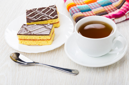 Cakes with chocolate on white plate, napkin, tea in cup on saucer, teaspoon on wooden table