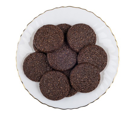 Round chocolate cookies with airy rice in glass plate isolated on white background. Top view Banco de Imagens