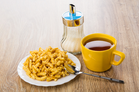 Heap of chuck-chuck with sesame in white plate, cup of tea, teaspoon, sugar bowl on wooden table Stock Photo