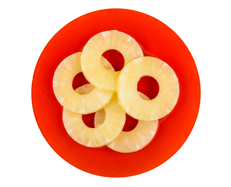Rings of canned pineapple in red plate isolated on white background. Top view Banco de Imagens
