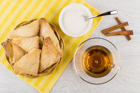 Puff pastry in wicker basket, cup of tea, sugar, spoon in bowl, cinnamon sticks on wooden table. Top view Stock fotó - 106350626