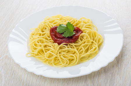 Boiled spaghetti with ketchup and cilantro in white plate on wooden table Stok Fotoğraf