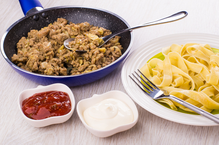 Noodles, fork in plate, bowls with ketchup, mayonnaise, fried mincemeat in frying pan on wooden table