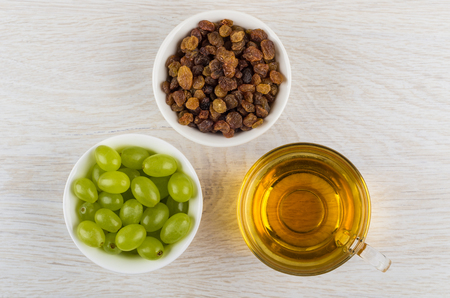 Small bowls with berries of grape and raisins, cup with grape juice on wooden table. Top view
