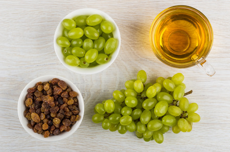 Small bowls with berries of grape and raisins, cup with grape juice, bunch of grapes on wooden table. Top view