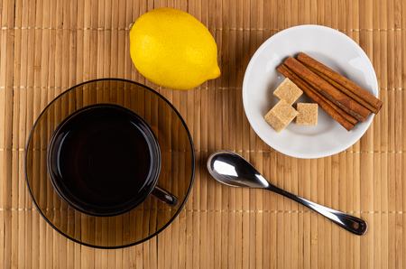 Cup of tea on saucer, lemon, spoon, bowl with cinnamon sticks, sugar cubes on mat. Top view 免版税图像