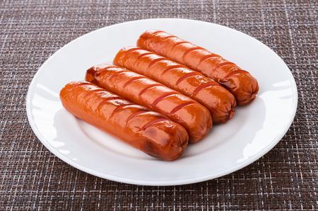 Quelques saucisses grillées dans une assiette blanche sur un tapis sombre