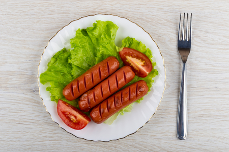 Grilled sausages, lettuce, tomato in white plate, fork on wooden table. Top view 版權商用圖片