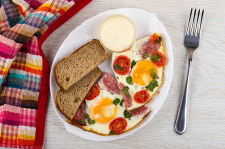 Fried eggs with sausages and tomato, pieces of bread, bowl with mayonnaise in white plate, napkin, fork on wooden table. Top view