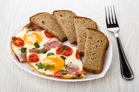 Fried eggs with sausages and tomato, pieces of bread in white plate, fork on wooden table