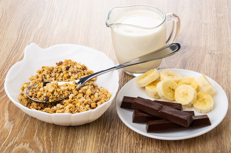 Muesli, spoon in white bowl, pieces of chocolate and banana in saucer, jug of milk on wooden table