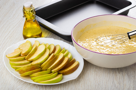 Slices of apples in plate, dough, whisk in bowl, baking tray, bottle of vegetable oil on wooden table Stockfoto - 112521831
