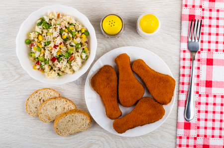 Bowl with vegetable mix, cutlet in plate, mayonnaise, pepper, pieces of bread, fork on napkin on wooden table. Top view