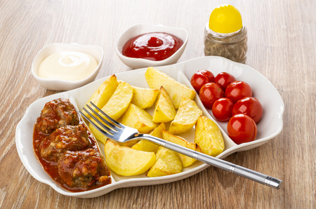 Fish meatballs with fried potato and marinated tomatoes, fork in white dish, bowls with mayonnaise, ketchup, pepper on wooden table