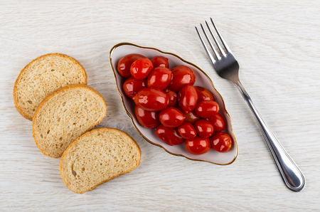 Marinated tomato cherry in plate, pieces of bread, fork on wooden table. Top view