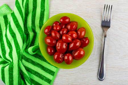 Marinated tomato cherry in green bowl, striped napkin, fork on wooden table. Top view 写真素材