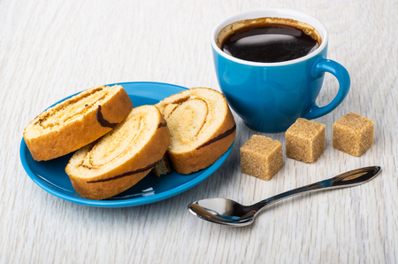 Slices of swiss roll in saucer, coffee in cup, spoon, sugar cubes on wooden table