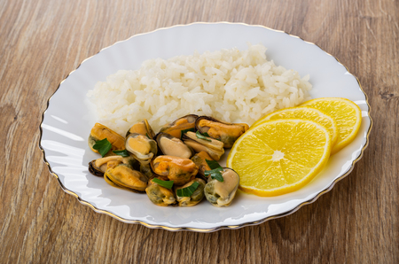 Cooked mussels with rice, lemon and parsley in plate on wooden table