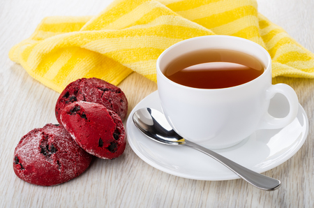 Red shortbread cookies, cup of tea, teaspoon on saucer, yellow napkin on wooden table