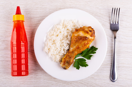 Grilled chicken leg with rice and parsley in white plate, bottle of ketchup, fork on wooden table. Top view