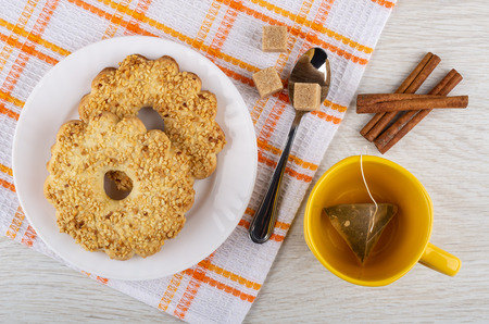 Shortbread rings with peanut in white plate, sugar cubes, teaspoon on checkered napkin, tea bag in yellow cup, cinnamon sticks on wooden table. Top view