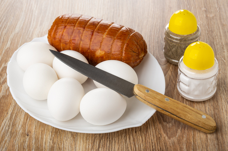 Sausage, chicken eggs in white plate, kitchen knife, salt shaker, pepper shaker on wooden table