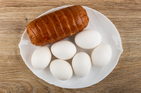 Sausage, chicken eggs in white plate on wooden table. Top view Фото со стока