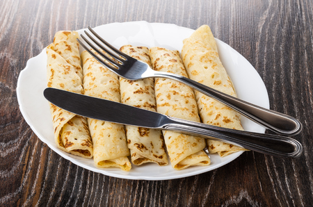 Knife and fork on white glass dish with pancake rolls on dark wooden table