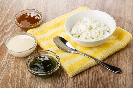 Bowl with cottage cheese, teaspoon on yellow napkin, bowls with boiled condensed milk, condensed milk, gooseberry jam on wooden table