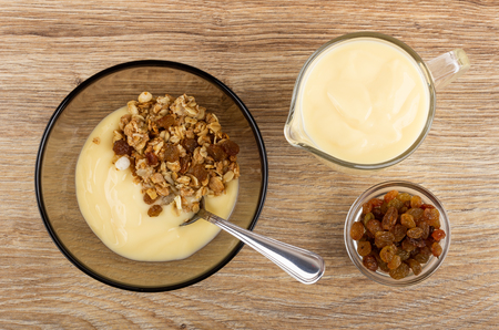 Spoon in brown bowl with muesli and yogurt, jug of yogurt, bowl with raisin on wooden table. Top view Imagens