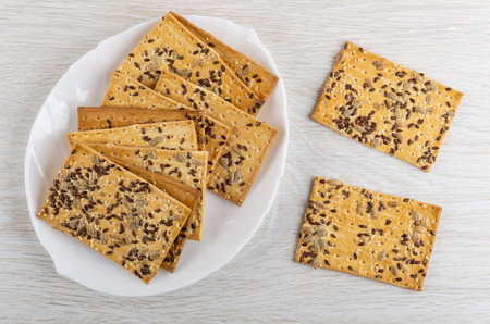 Heap of cookies with sunflower seeds, flax-seeds, sesame in dish and on wooden table. Top view Reklamní fotografie