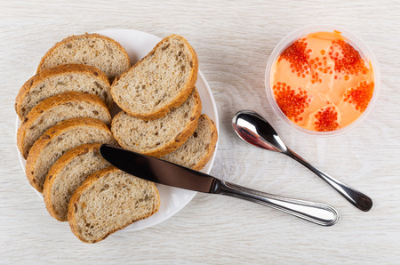 Pieces of bread in white plate, table knife, spoon, imitation of red caviar with cream in plastic jar on wooden table. Top view