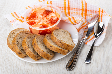 Pieces of bread, imitation of red caviar with cream in plastic jar on white plate, knife and spoon on napkin on wooden table