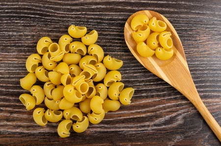 Heap uncooked pasta lumache, pasta in bamboo spoon on wooden table. Top view