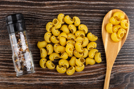 Jar with condiment, heap uncooked pasta lumache, pasta in bamboo spoon on wooden table. Top view Stock Photo