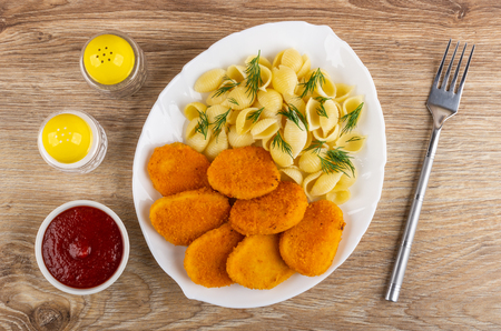 Bowl with ketchup, pepper and salt shakers, fried chicken nuggets with pasta and dill in white dish, fork on wooden table. Top view