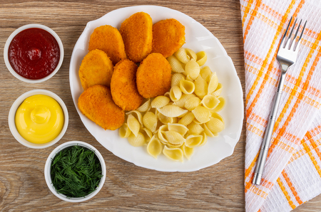 Bowls with ketchup, mayonnaise, dill, fried chicken nuggets with pasta in white dish, fork on checkered napkin on wooden table. Top view