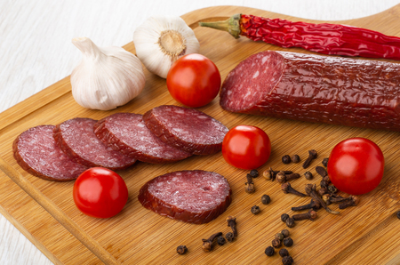 Slices of smoked sausage, garlic, chili pepper, black pepper, clove spice, tomato cherry on cutting board on wooden table
