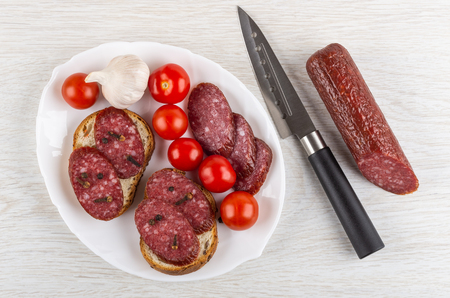 Tomato cherry, garlic, sandwiches with smoked sausage in white plate, kitchen knife on wooden table. Top view