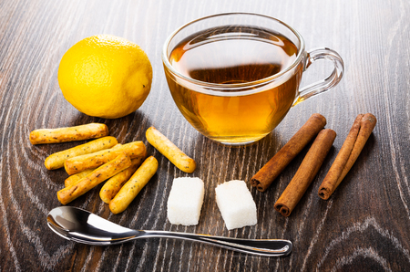 Bread sticks with poppy, lemon, cup of tea, teaspoon, sugar cubes, cinnamon sticks on dark wooden table