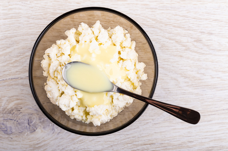 Bowl of cottage cheese with sweet condensed milk, spoon on wooden table. Top view Imagens