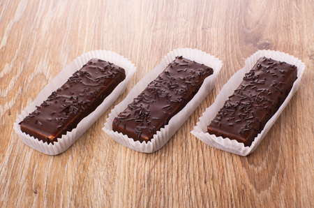 Chocolate wafers in paper wrapper on wooden table