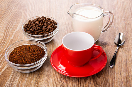 Bowls with ground coffee and coffee beans, spoon, empty red cup on saucer on wooden table
