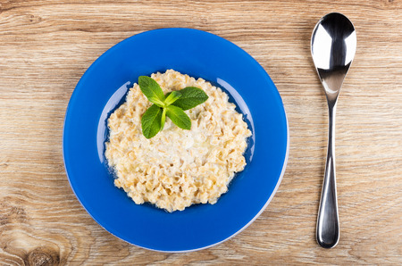 Oatmeal with milk and leaves of mint in blue plate, spoon on wooden table. Top view