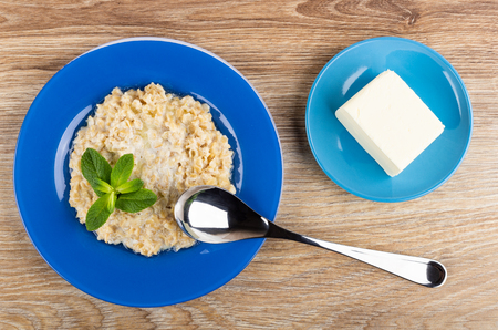Oatmeal with milk and leaves of mint in blue plate, spoon, saucer with piece of butter on wooden table. Top view Stock Photo
