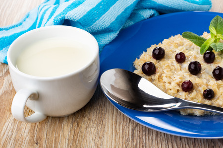 Oatmeal with milk, blackcurrant and leaves of mint, spoon in blue plate, striped napkin, cup of milk on wooden table