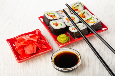 Vegetable rolls with sweet pepper, cucumber, carrot and lettuce, wasabi in red ceramic plate, sticks, soy sauce in bowl, pickled ginger in plate on wooden table Imagens