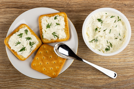 Crackers with soft cheese and greens in saucer, soft cheese with dill in white plastic jar, spoon on wooden table. Top view